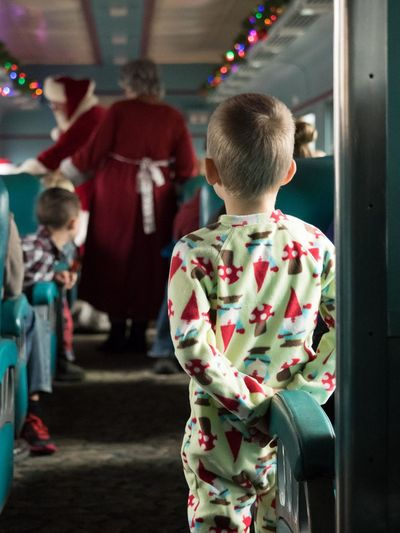 Rear view of boy looking at people dressed as santa claus in train