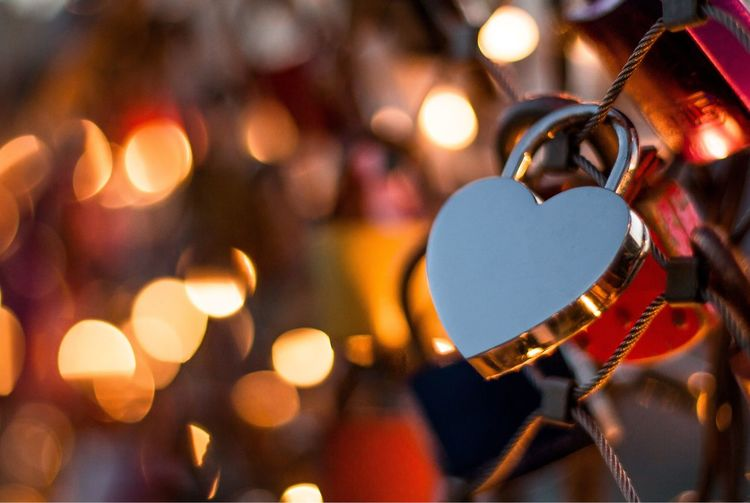 Close-Up Of Heart Shape Love Lock On Railing During Christmas At Night