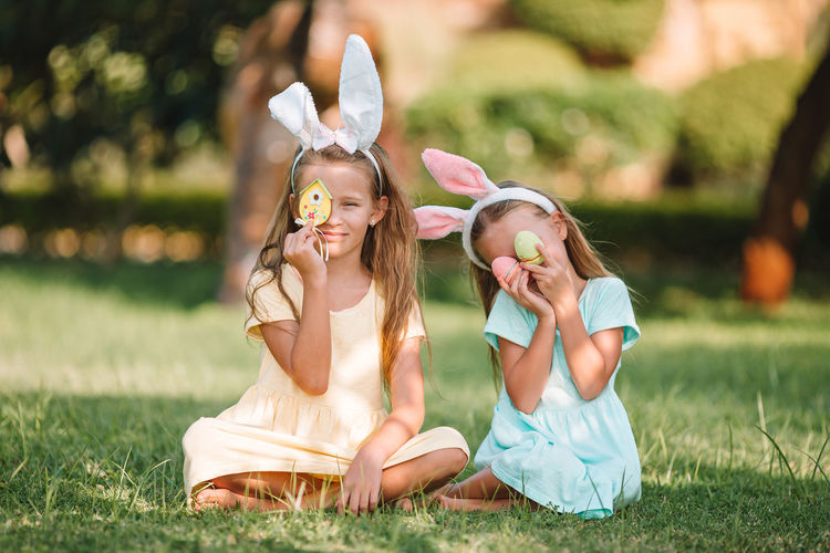 Sisters holding easter eggs while sitting at lawn