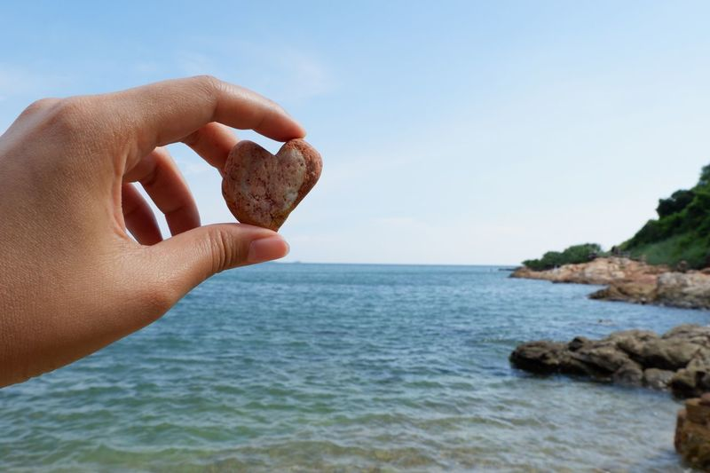 Cropped hand of woman holding heart shape pebble against sea and sky