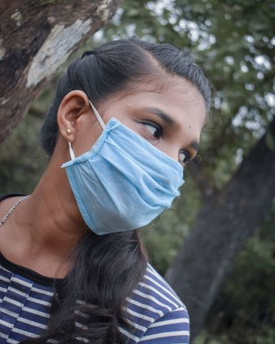 Close-up of young woman wearing mask looking away outdoors
