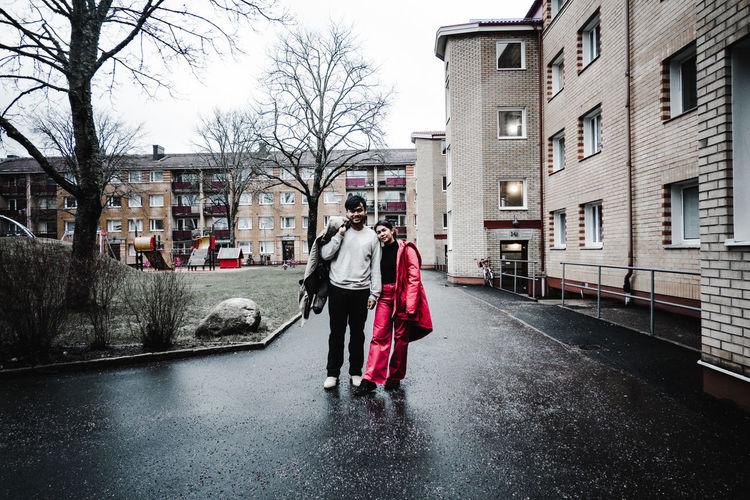 Rear view of women walking on wet street in city