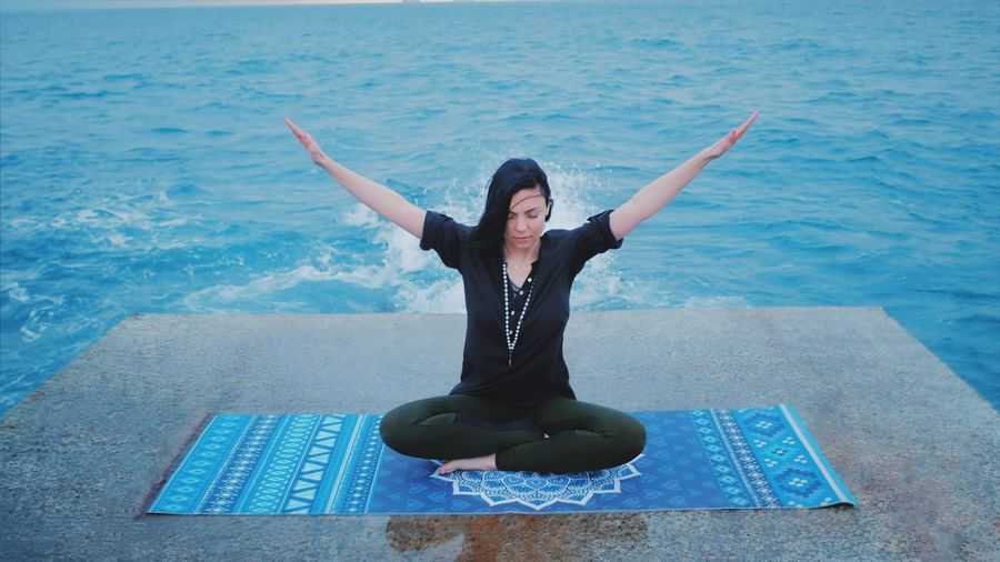 Full Length Of Woman Performing Yoga Against Sea