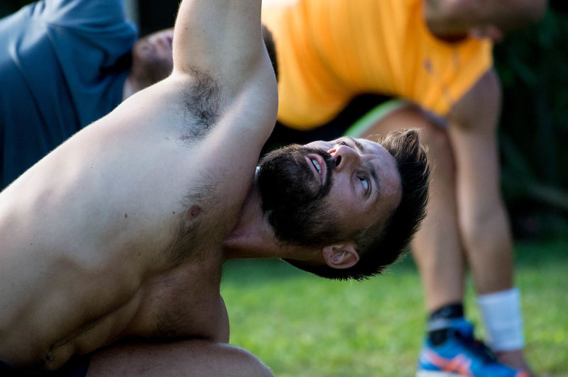 Close-up of shirtless man with friends exercising in lawn