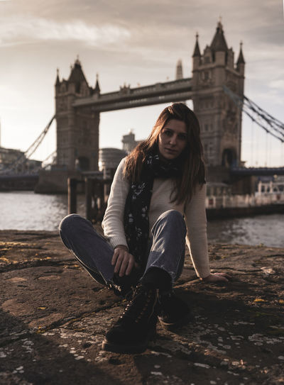 Woman sitting on bridge over river in city