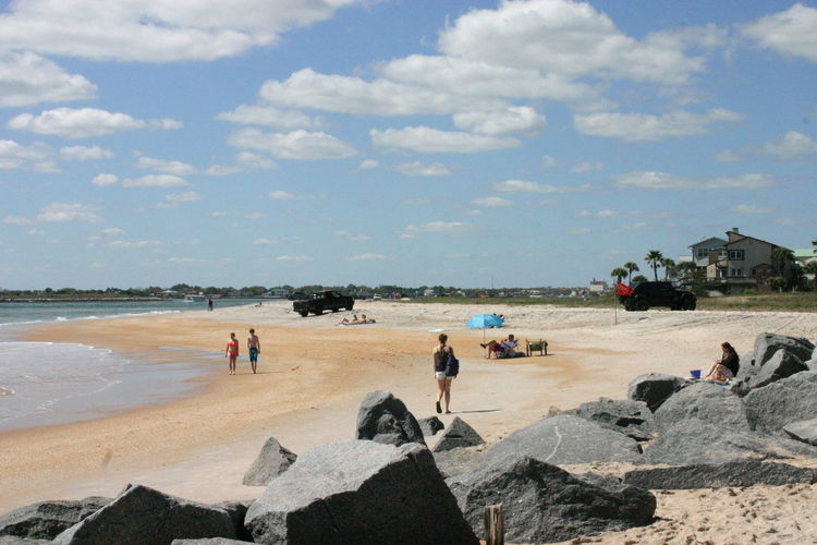 People visiting beach against sky