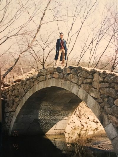 Full length of woman standing on arch bridge