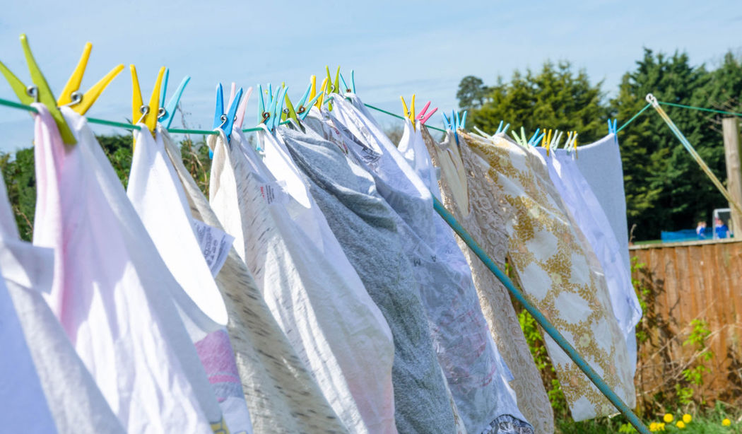 Laundry hanging outside in the back garden to dry on a washing line. Back Garden Chores Close-up Clothes Clothes Pegs Clothesline Day Drying Freshness Hanging Laundry Laundry Pegs No People Out Outdoors People Sky Sunlight Washing Washing Line