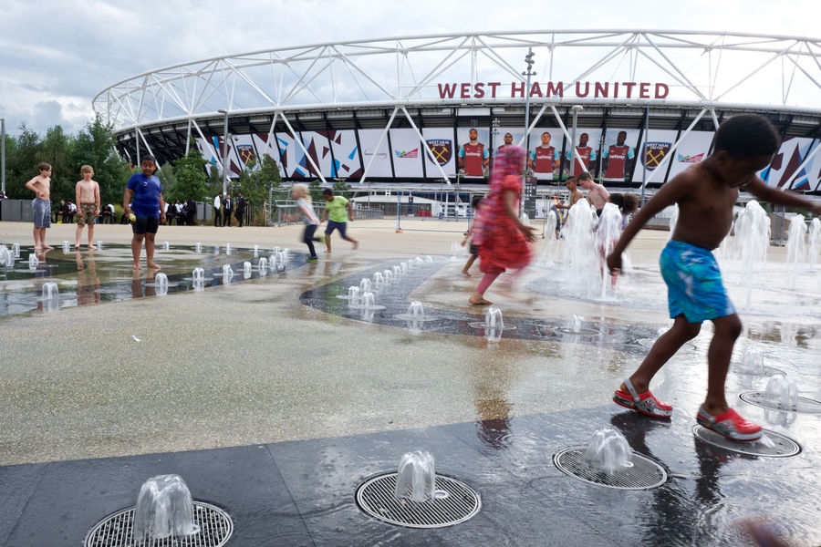 young people play in the hot sunshine in the shadow of west ham football club Children City City Life East London Enjoyment Football Fountain Fun Leisure Activity London London Stadium Mixed Age Range Motion Olympic Park  Olympic Stadium Playing Soccer Stratford Summer Sunshine Uk Water West Ham Utd
