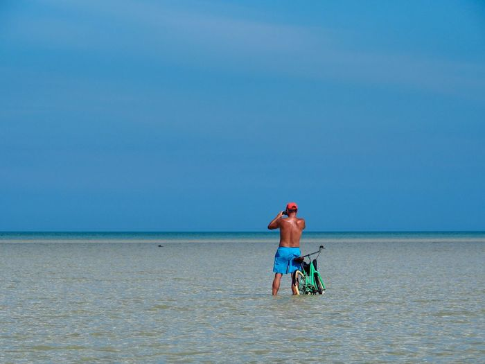 Sea Water Horizon Over Water Sky Horizon One Person Land Full Length Beach Nature Day Beauty In Nature Clear Sky Shirtless Holiday Copy Space Trip Blue Outdoors Bicycle Ocean Photography Vacations