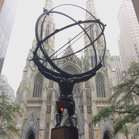 Statue of Atlas at the Rockefeller centre with St Patrick's catherdral in the background. New York City, United States of America. City Architecture Building Exterior Built Structure Outdoors Day Low Angle View New York City Landmark NYC Tourism Sculpture Sky Statue