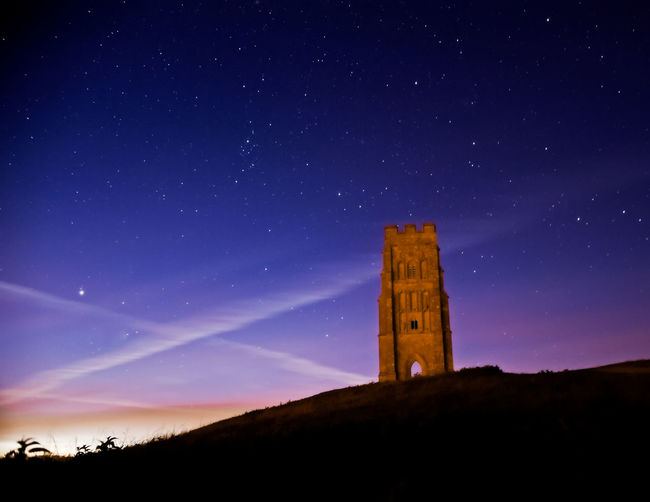 Glastonbury Tor Architecture Atmospheric Mood Beauty In Nature Blue Building Exterior Built Structure Church Constellation History Low Angle View Moon Mystical Nature Night No People Outdoors Place Of Worship Religion Scenics Sky Spirituality Star - Space Sunrise Tor Tower