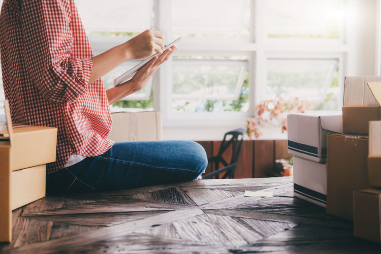 Midsection Of Woman Holding Digital Tablet While Sitting By Cardboard Boxes On Table