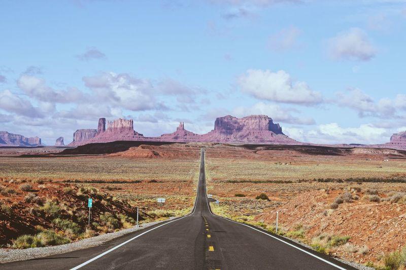 Empty road along landscape against sky