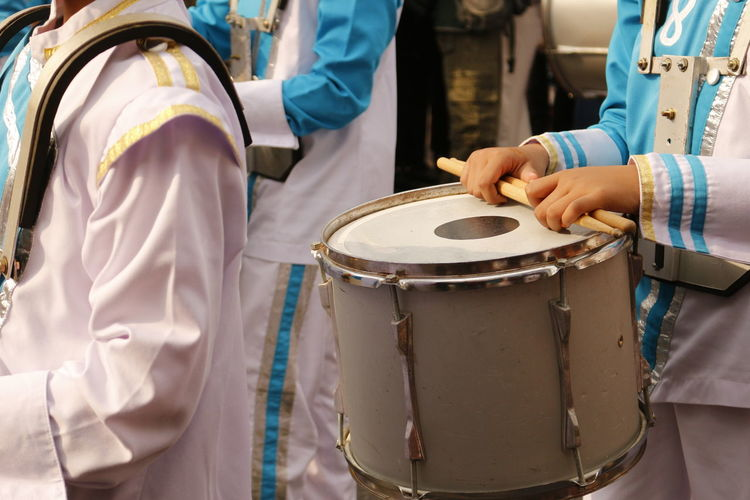 Marching band player carrying snare drum