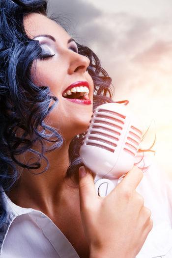 Woman singing in microphone against sky
