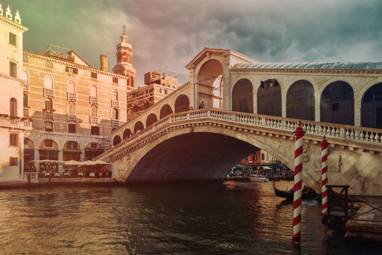 Low angle view of rialto bridge over grand canal against cloudy sky