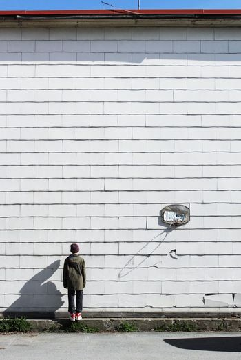 Rear View Of Boy Standing Against White Wall
