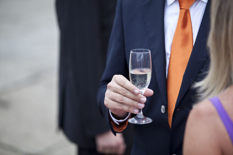 Midsection of man holding drink at event