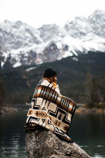 Person standing on rock by lake during winter