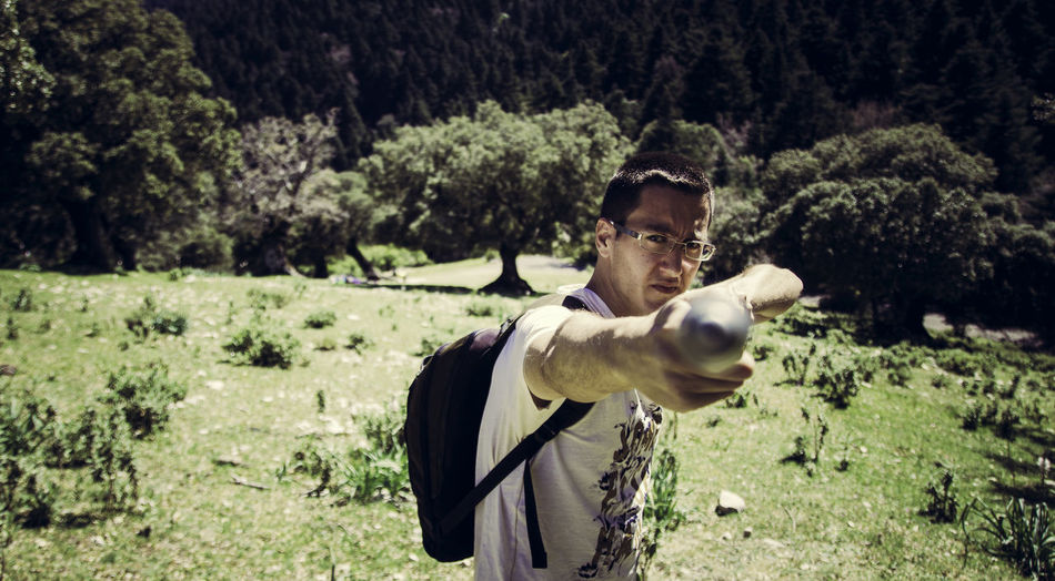 Portrait of male hiker pointing stick while standing on grassy field