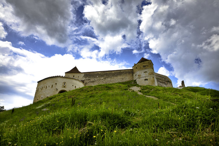 Low angle view of bran castle on top of mountain against cloudy sky