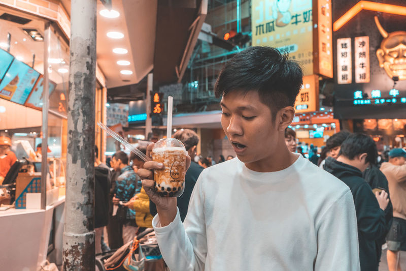 Incidental People Market Real People Illuminated Retail  Lifestyles Focus On Foreground Young Adult Young Men Casual Clothing Men Leisure Activity People Food And Drink Waist Up Business City Looking Outdoors Retail Display
