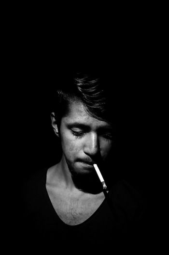 Portrait of young man smoking over black background