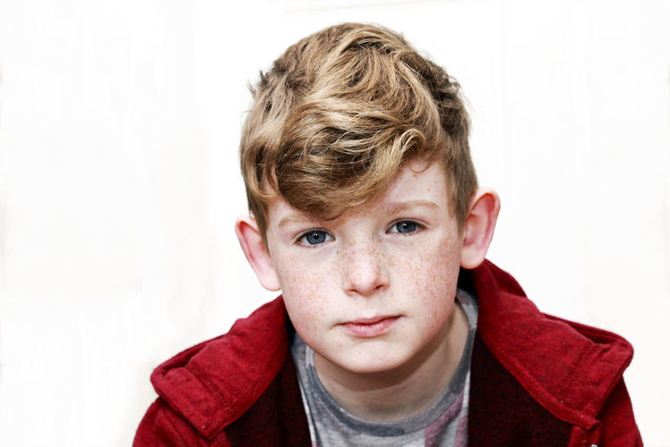 Portrait of a boy. Young Youth Boys Casual Clothing Child Childhood Contemplation Emotion Front View Hair Headshot Indoors  Innocence Lifestyles Looking At Camera Male One Person Portrait Pre-adolescent Child Studio Shot White Background