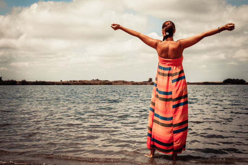 Rear view of woman standing with arm outstretched and having fun at the beach in summer day.