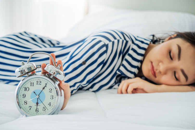 Woman sleeping with clock on bed at home