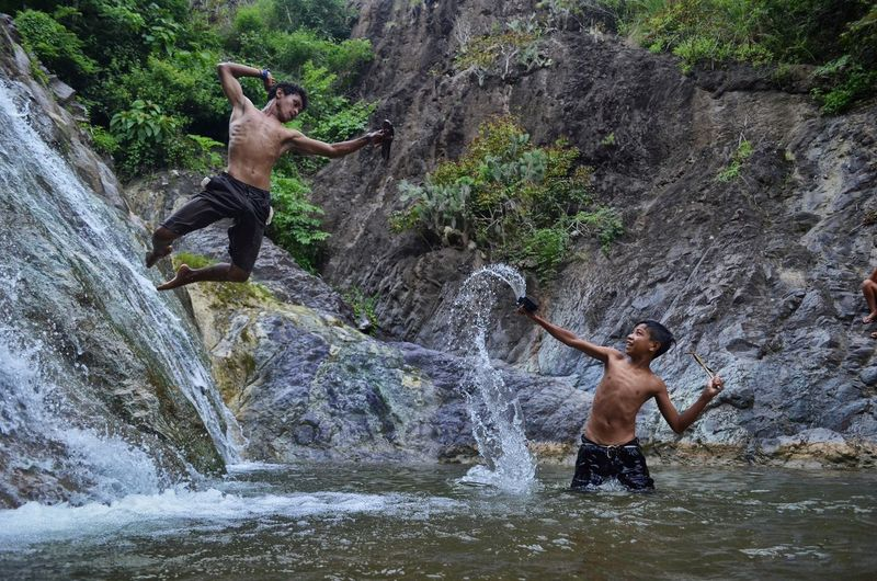 Full length of shirtless man standing on rock against waterfall