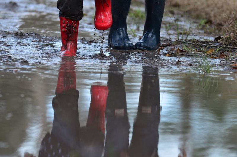 Low section of people standing in puddle