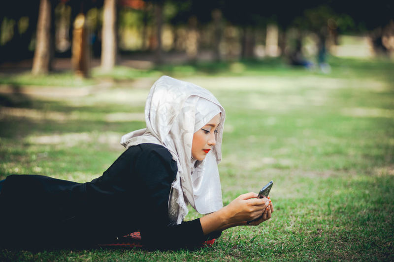 Side View Of Woman Wearing Hijab While Using Mobile Phone On Grassy Field At Park