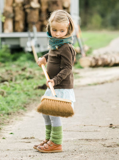 Side view of girl holding broom while standing on road