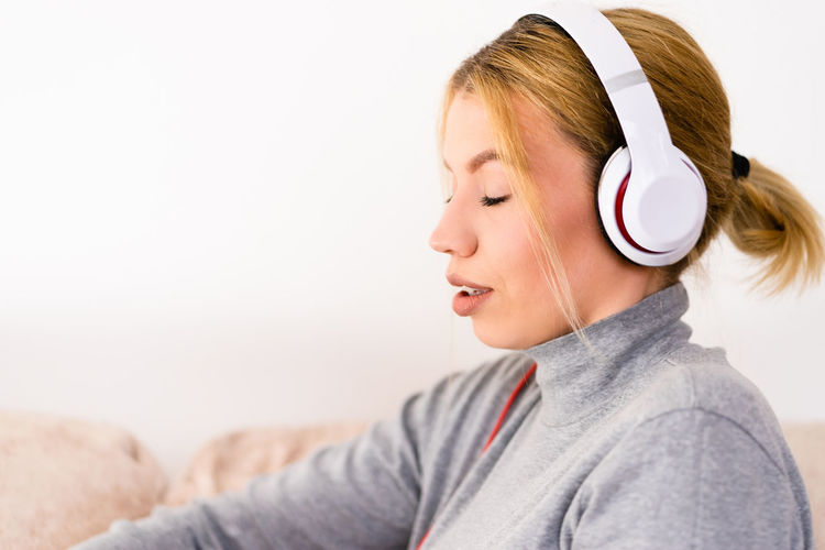 Headphones One Person Music Indoors  Headshot Listening Portrait Adult Lifestyles Smiling Leisure Activity Young Adult Casual Clothing Copy Space Relaxation Clothing Women Sweater Hairstyle Profile View Teenager