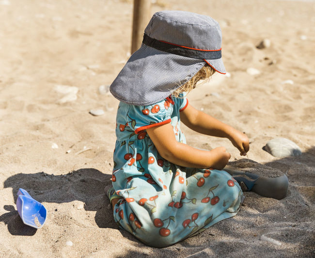 Cute girl playing with sand at beach