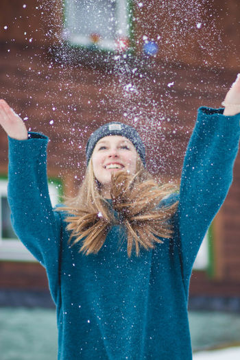 Close-up of woman playing with snow