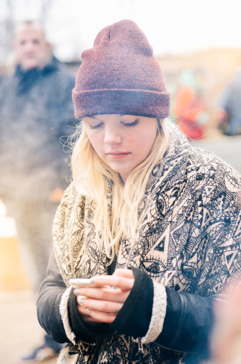 real people, knit hat, lifestyles, leisure activity, waist up, front view, warm clothing, casual clothing, focus on foreground, young women, outdoors, blond hair, one person, scarf, day, looking at camera, young adult, close-up, wireless technology, portrait