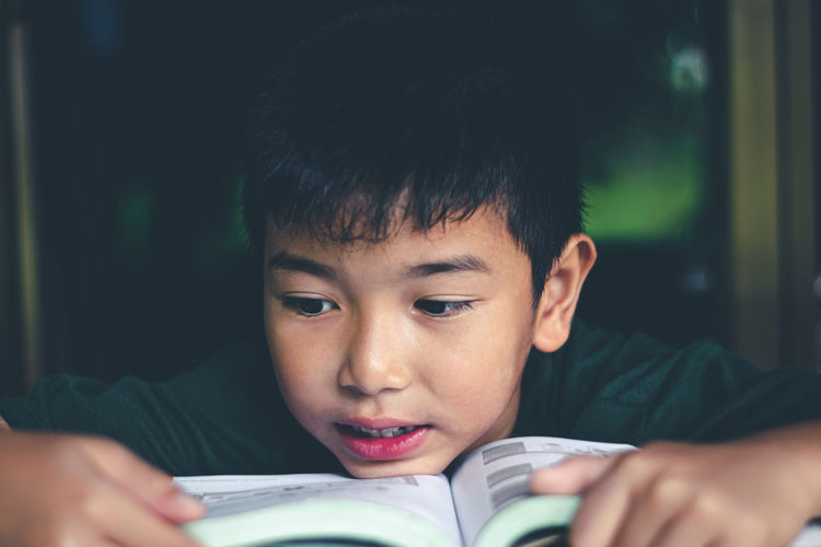 Portrait of boy looking at book