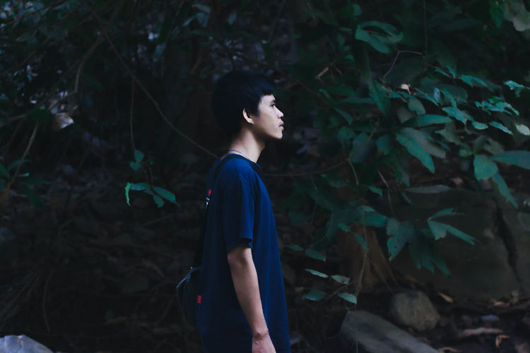Side view of young man looking away in forest