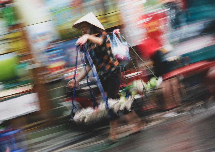 Blurred motion of woman walking on road in city