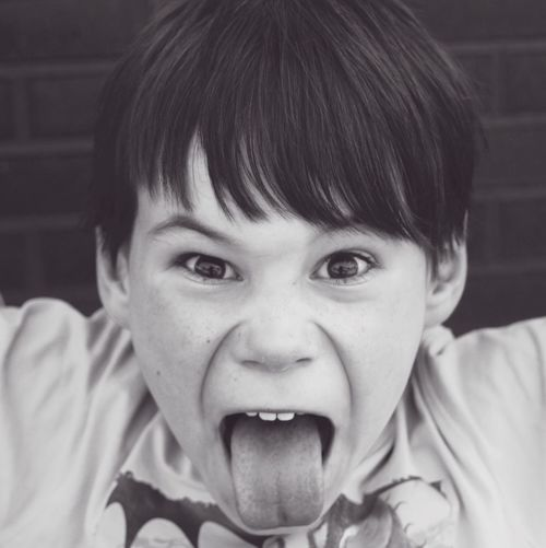 Close-up portrait of angry boy sticking out tongue