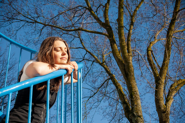 Low angle view of woman looking at bare tree against blue sky
