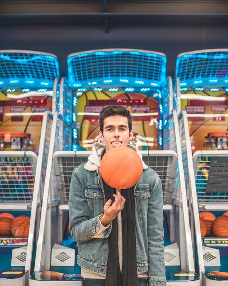 Portrait of young man spinning basketball against amusement arcades