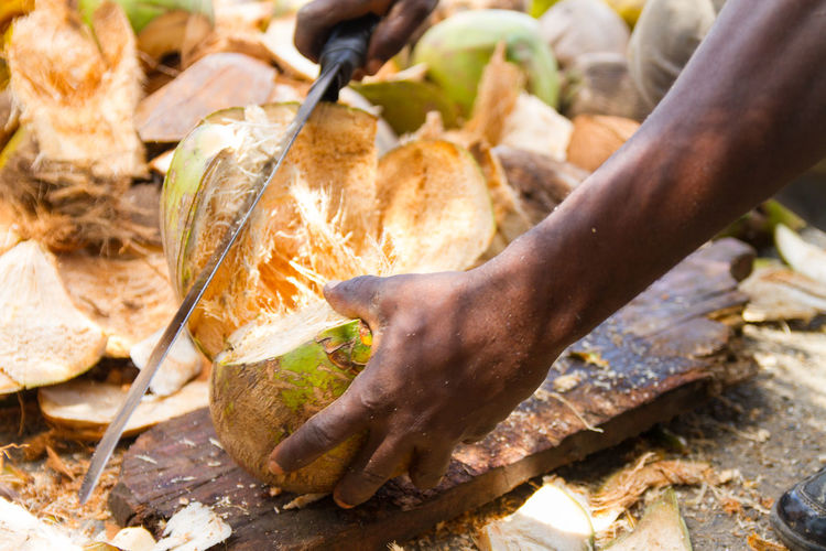 Cropped man cutting coconut with machete on board
