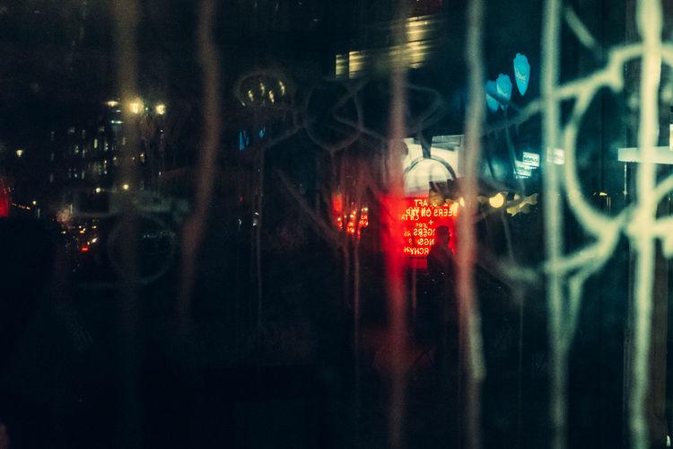 Illuminated street seen through glass window