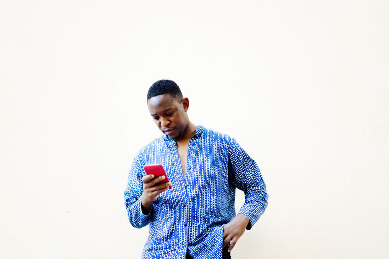 Young man using mobile phone against white background