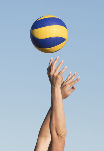 Low angle view of person hand against blue sky with ball