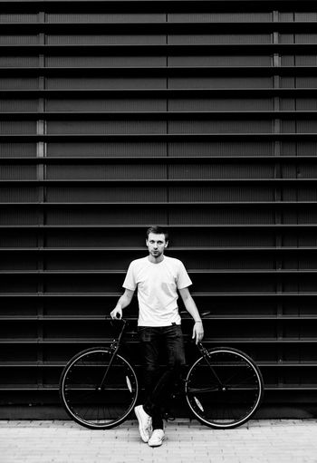 Portrait of young man standing by bicycle against wall